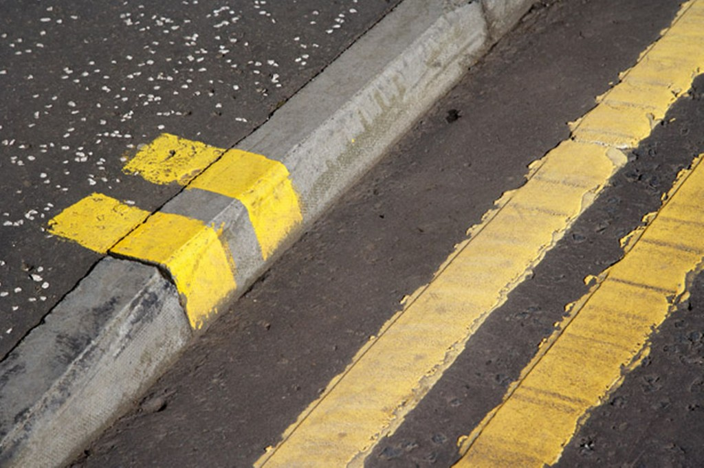 Double-yellow-lines-on-a-road-and-pavement-curb-2101582
